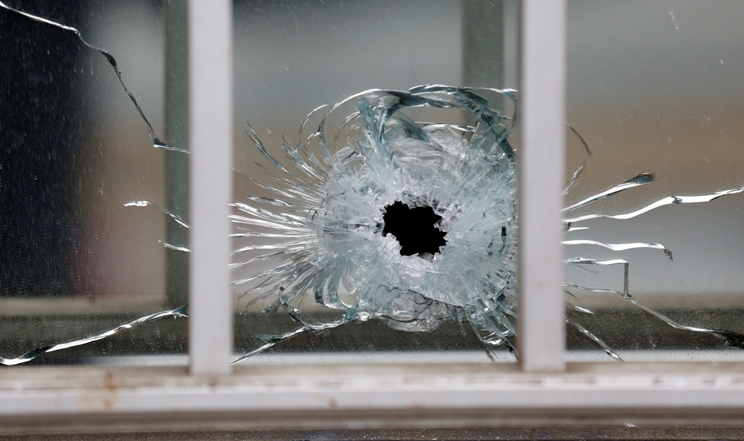 A bullet's impact is seen on a window at the scene after a shooting at the Paris offices of Charlie Hebdo, a satirical newspaper, January 7, 2015. Eleven people were killed and 10 injured in shooting at the Paris offices of the satirical weekly Charlie Hebdo, already the target of a firebombing in 2011 after publishing cartoons deriding Prophet Mohammad on its cover, police spokesman said. Five of the injured were in a critical condition, said the spokesman. Separately, the government said it was raising France's national security level to the highest notch.    REUTERS/Jacky Naegelen (FRANCE - Tags: CRIME LAW MEDIA) - RTR4KDIY